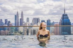 Jonge vrouw in openlucht zwembad met stadsmening in blauwe hemel Rijken stock fotografie