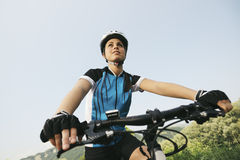 Jonge vrouw opleiding op bergfiets en het cirkelen in park Royalty-vrije Stock Afbeelding