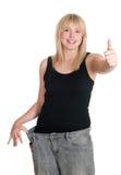 Jonge vrouw in overmaats broek verloren gewicht royalty-vrije stock afbeeldingen