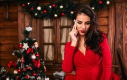 Jonge vrouw in rode kleding die op mobiele telefoon spreken Royalty-vrije Stock Afbeeldingen