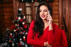 Jonge vrouw in rode kleding die op mobiele telefoon spreken Royalty-vrije Stock Foto