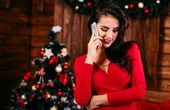 Jonge vrouw in rode kleding die op mobiele telefoon spreken Stock Afbeelding