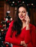 Jonge vrouw in rode kleding die op mobiele telefoon spreken Royalty-vrije Stock Foto's