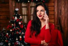 Jonge vrouw in rode kleding die op mobiele telefoon spreken Stock Afbeeldingen