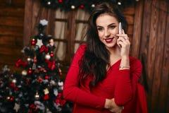 Jonge vrouw in rode kleding die op mobiele telefoon spreken Stock Fotografie