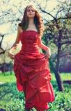 Jonge vrouw in rode kleding in tuin Royalty-vrije Stock Fotografie