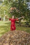Jonge vrouw in rode kleding Werp omhoog de de herfstbladeren royalty-vrije stock afbeeldingen