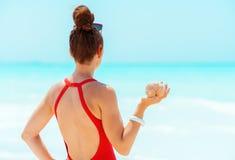 Jonge vrouw in rode swimwear met overzeese shell op zeekust stock afbeelding