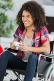 Jonge vrouw in rolstoel het spelen videospelletjes thuis royalty-vrije stock foto