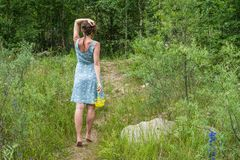 Jonge vrouw in romantische blauwe kleding met gele bloemen in mo Stock Afbeeldingen