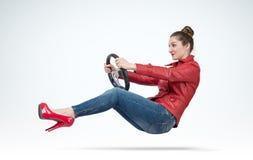 Jonge vrouw in rood leerjasje met autostuurwiel, autoconcept Royalty-vrije Stock Fotografie