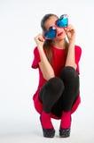 Jonge vrouw in rood met hart gevormde glazen Stock Foto's