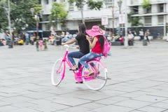 Jonge vrouw in roze hoed die een fiets in stad berijden Actieve mensen outdoors Stock Afbeeldingen