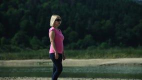 Jonge vrouw in roze kleding en zonnebril die naast een rivier bezienswaardigheden bezoeken stock videobeelden