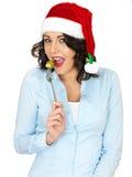 Jonge Vrouw in Santa Hat Eating een Spruitje van een Vork stock afbeelding