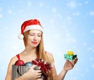 Jonge vrouw in santahoed met Kerstmisattributen en weinig gi Stock Foto's