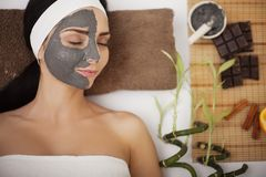 Jonge vrouw in schoonheidssalon die gezichtsmasker hebben Royalty-vrije Stock Afbeelding