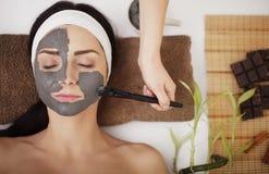 Jonge vrouw in schoonheidssalon die gezichtsmasker hebben Royalty-vrije Stock Afbeeldingen