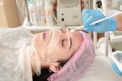 Jonge vrouw in schoonheidssalon die ultrasone klankschil en gezichts het reinigen procedure doen stock afbeeldingen