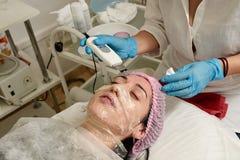 Jonge vrouw in schoonheidssalon die ultrasone klankschil en gezichts het reinigen procedure doen royalty-vrije stock afbeelding
