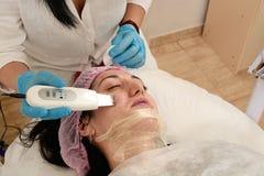 Jonge vrouw in schoonheidssalon die ultrasone klankschil en gezichts het reinigen procedure doen stock afbeelding