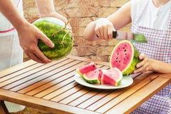 Jonge vrouw in schort die verse rijpe sappige rode watermeloen snijden stock foto's