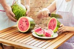 Jonge vrouw in schort die verse rijpe sappige watermeloen snijden stock foto