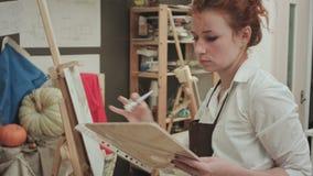 Jonge vrouw in schort het schilderen met olie op wit canvas stock videobeelden