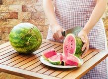 Jonge vrouw in schort snijdende watermeloen op houten lijst royalty-vrije stock foto's