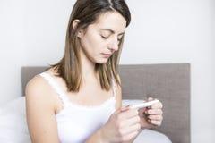 Jonge vrouw in slaapkamer die thuis in witte controle zwangere test dragen royalty-vrije stock fotografie