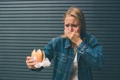 Jonge vrouw snel voedsel eten openlucht en zeer slechte gevoel die royalty-vrije stock fotografie