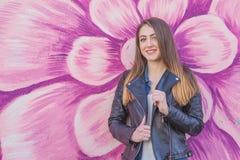 Jonge vrouw in stedelijk landschap - graffiti Stock Foto's