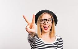 Jonge vrouw in studio op een witte achtergrond, die een teken van vrede tonen royalty-vrije stock afbeeldingen