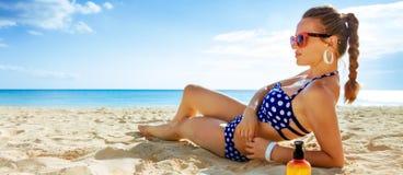 Jonge vrouw in swimwear bij zeekust het zonnebaden stock afbeeldingen