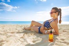 Jonge vrouw in swimwear bij zeekust het zonnebaden stock foto