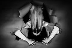 Jonge vrouw tearing aan stukken een muur van document stock fotografie