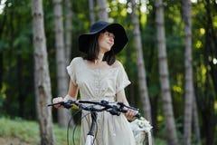 Jonge vrouw tegen aardachtergrond met fiets Stock Afbeeldingen