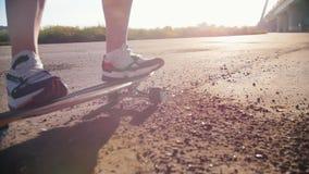 Jonge vrouw in tennisschoenen die skateboard berijden op het vuil stock footage
