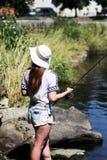 Jonge vrouw terwijl visserij op een rivier in Beieren Royalty-vrije Stock Foto