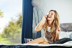 Jonge vrouw thuis met telefoon Stock Fotografie