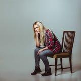 Jonge vrouw in toevallige uitrustingszitting op stoel Stock Foto's