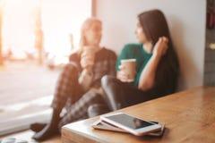 Jonge vrouw twee die in een koffiewinkel babbelen Twee vrienden die van koffie samen genieten Hun smartphones die in stapel ligge Stock Afbeelding