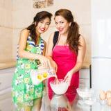 Jonge vrouw twee die pannekoeken maken royalty-vrije stock foto's