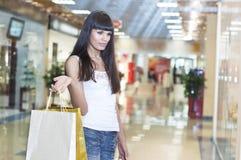 Jonge vrouw in wandelgalerij het kopen kleren Stock Afbeeldingen