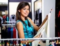 Jonge vrouw in winkel het kopen kleren Stock Foto