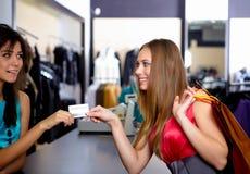 Jonge vrouw in winkel het kopen kleren Stock Foto's