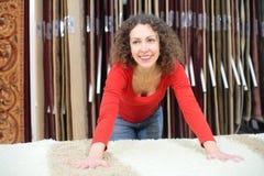 Jonge vrouw in winkel met pluizig tapijt royalty-vrije stock afbeelding