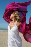 Jonge vrouw in wit op strand met het rode fladderen Royalty-vrije Stock Foto's