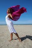 Jonge vrouw in wit op strand met het rode fladderen Stock Fotografie