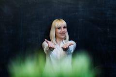 Jonge vrouw in wit overhemd die, die en haar handen glimlachen standhouden aan Royalty-vrije Stock Foto